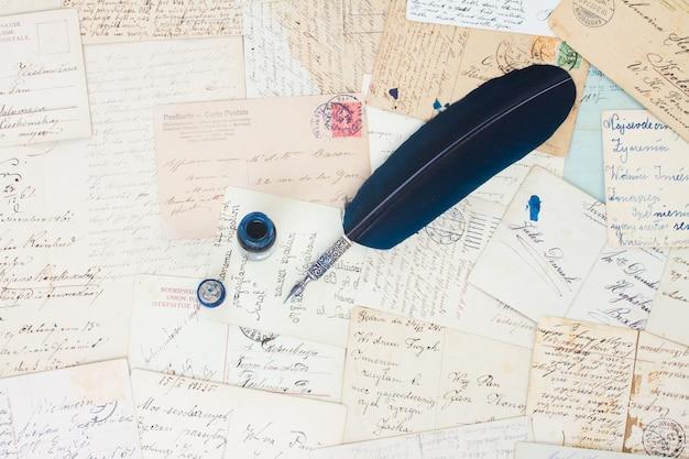 Caneta de pena azul em papel velho com fundo de letras antigas