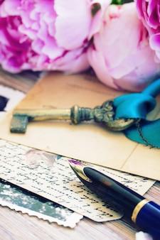 Caneta de pena dourada velha e letras antigas com flores de peônias e chave