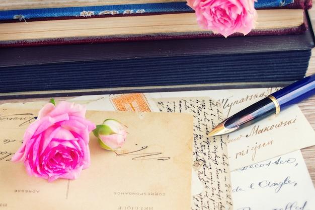 Caneta de pena dourada velha e letras antigas na mesa com livros e rosas
