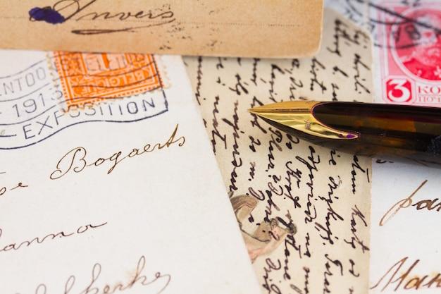 Caneta de pena dourada velha e letras antigas