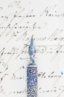 Caneta de pena velha no fundo de uma carta manuscrita.