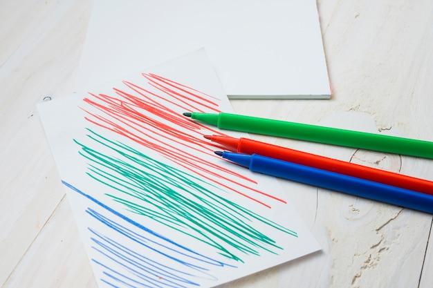 Caneta de ponta de feltro colorida e papel com traço de caneta na mesa de madeira branca