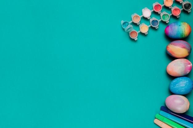 Caneta de ponta de feltro; garrafas plásticas de cor de água e ovos de páscoa pintados sobre fundo verde, com espaço de cópia