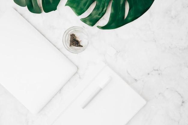Caneta; diário; tablet digital; folha de monstera e saquinho de chá no vidro na mesa de mármore