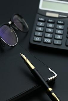 Caneta dourada, caderno, calculadora e óculos na mesa preta