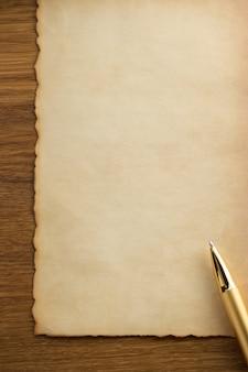 Caneta dourada em textura de pergaminho
