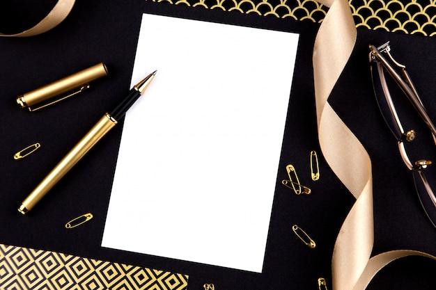Caneta dourada, fita, clipes de papel e papelaria em um fundo preto com uma folha branca de papel com espaço de cópia