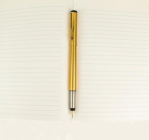 Caneta dourada no notebook ou no jornal para escritor