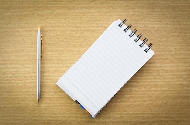 Caneta e bloco de notas com uma página em branco