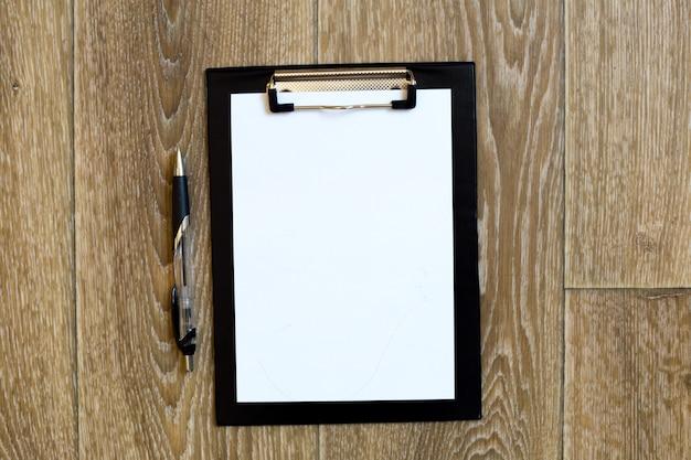 Caneta e bloco de notas na mesa de madeira