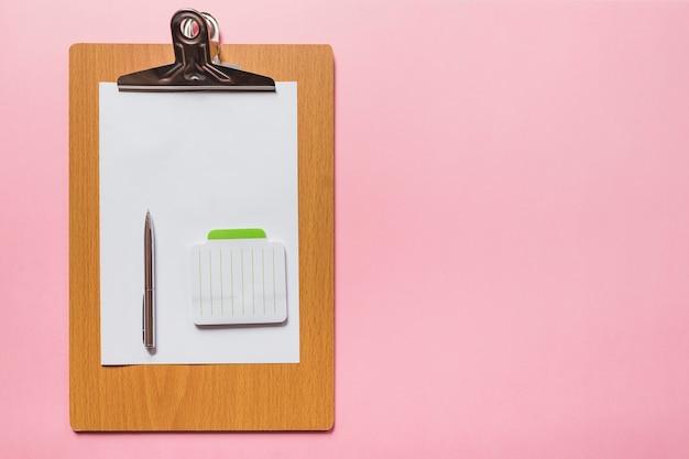 Caneta e bloco de notas no papel em branco sobre a prancheta de madeira contra um fundo rosa