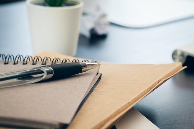 Caneta e caderno de perto em uma mesa de escritório