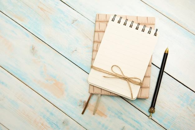 Caneta e caderno de perto em uma mesa de madeira rústica