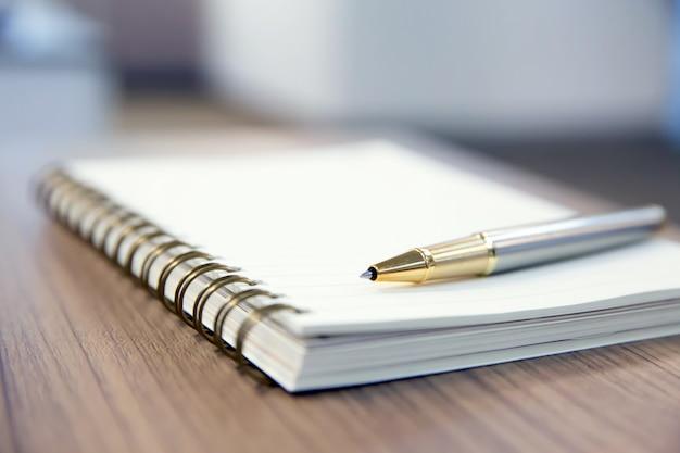 Caneta e caderno em cima da mesa.