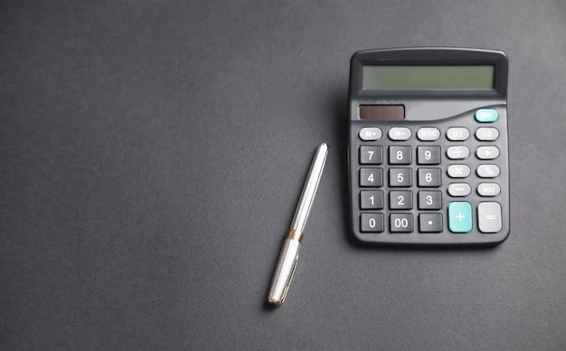 Caneta e calculadora no fundo preto.