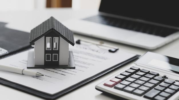 Caneta e casa modelo colocadas em documentos de contrato com calculadora e laptop, conceito de assinatura de contrato de construção de casa.
