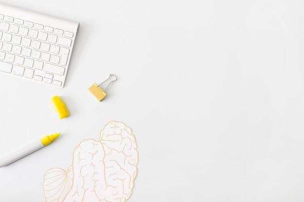 Caneta e clipe perto do teclado e adesivo