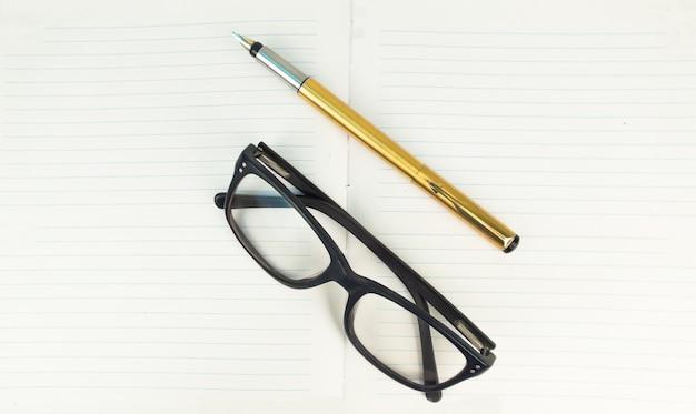 Caneta e especificações no caderno
