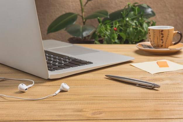 Caneta e fones de ouvido, laptop, xícara de café, mesa de madeira clara.