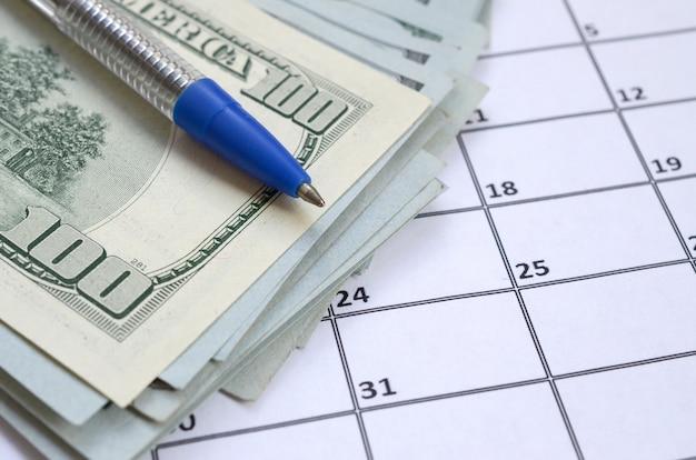 Caneta e muitas centenas de notas de dólar na página de calendário close-up