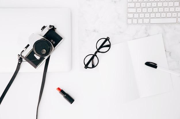 Caneta e óculos em papel; batom vermelho; câmera; teclado e tablet digital na mesa