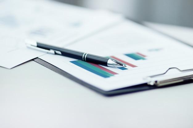 Caneta e relatório financeiro na mesa do escritório