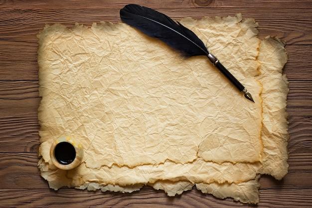 Caneta e tinta preta em papel velho em uma mesa de madeira