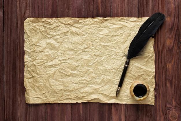 Caneta e tinta preta no fundo de um papel velho em uma mesa de madeira
