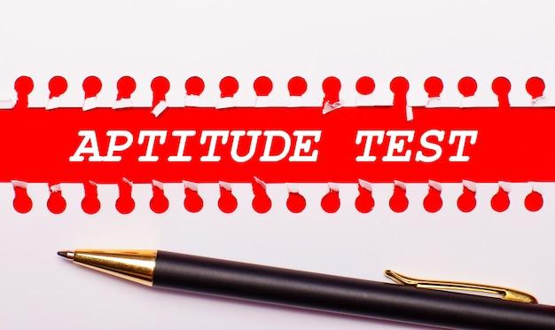 Caneta e tira de papel branca rasgada em um fundo vermelho brilhante com o texto teste de aptitude