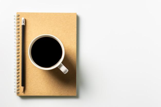 Caneta e uma xícara de café no livro diário na mesa. - trabalhe do conceito de casa.