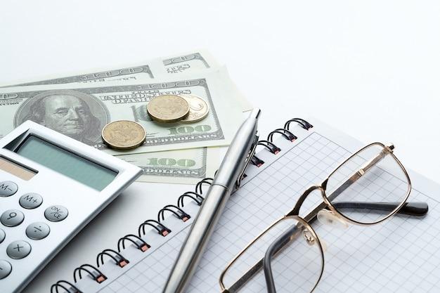 Caneta e vidros em um caderno aberto. ao lado estão notas de dólar e uma calculadora.