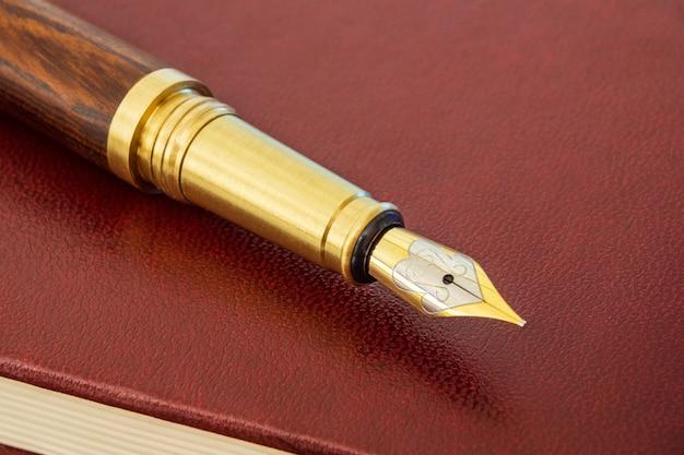 Caneta elegante com uma caneta banhada a ouro no bloco de notas marrom para anotações