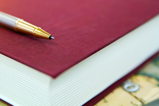 Caneta em cima do livro na mesa de escritório.