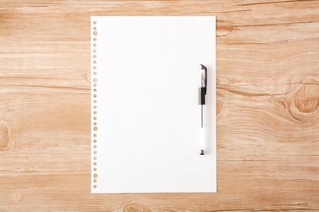 Caneta esferográfica anexada ao papel em branco de folhas soltas, colocado na mesa de madeira