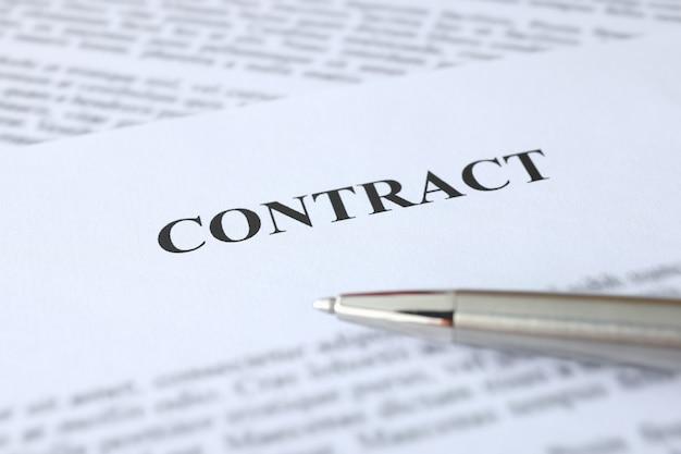 Caneta esferográfica de metal sobre documentos com contrato de emprego por conceito de contrato