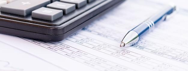 Caneta esferográfica e calculadora em um demonstrativo de planilha financeira com colunas de números para uma reconciliação de orçamento contábil e financeiro