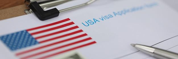 Caneta esferográfica e notas de dólar em documentos para solicitação de visto.