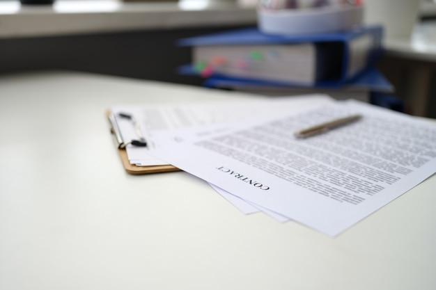 Caneta esferográfica sobre documentos com close do contrato