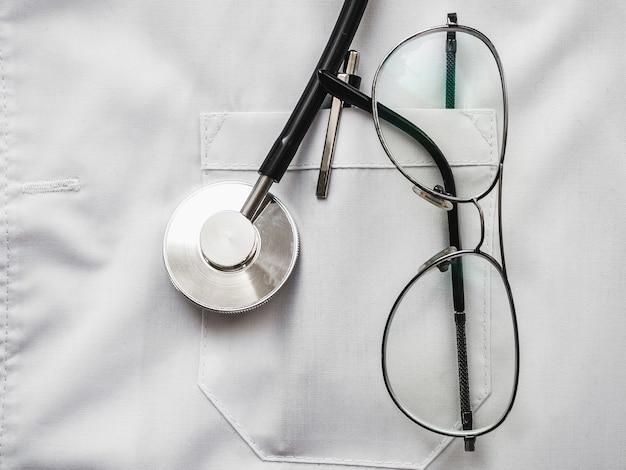 Caneta, estetoscópio, máscara facial e óculos, deitado em um vestido médico.