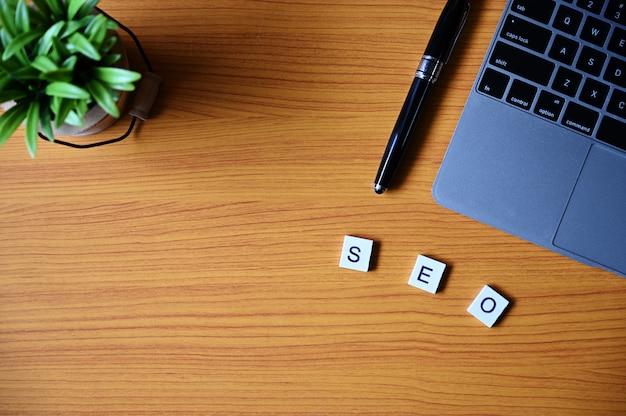 Caneta, laptop, planta e quadrados de madeira, formando uma palavra na mesa de madeira
