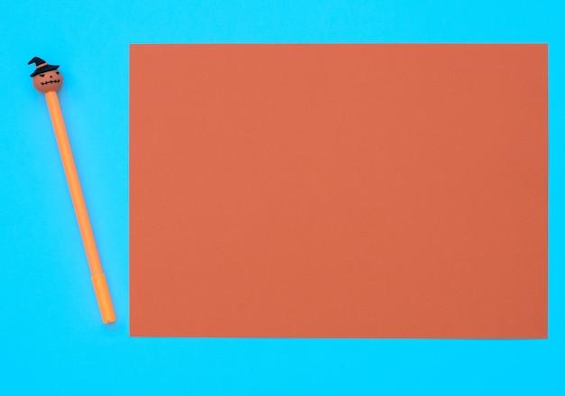 Caneta laranja com abóbora decorativa em fundo azul com folha laranja. conceito de halloween. estilo liso leigo com espaço de cópia.
