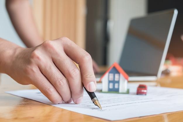 Caneta lida com documentos assinados com casas modelo, modelo de carro e laptop na mesa.