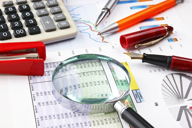 Caneta, lupa e o documento de trabalho com um diagrama