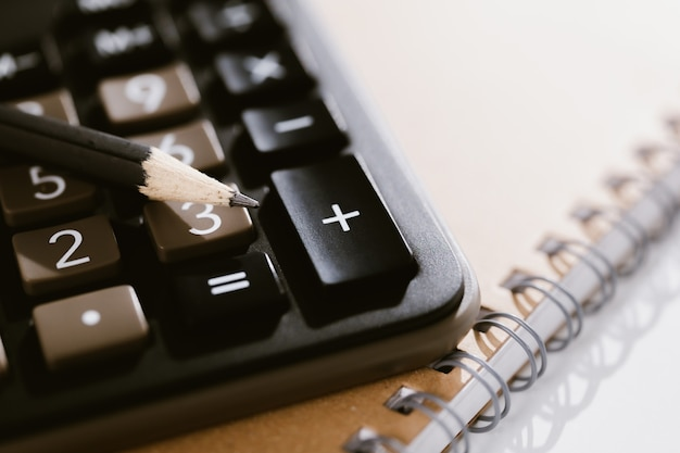 Caneta na calculadora e caderno em segundo plano, conceitos de gestão tributária e serviços de contabilidade.