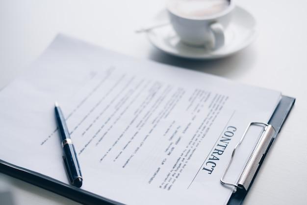 Caneta na folha de contrato e documento de negócios, perto de uma xícara de café no escritório em casa
