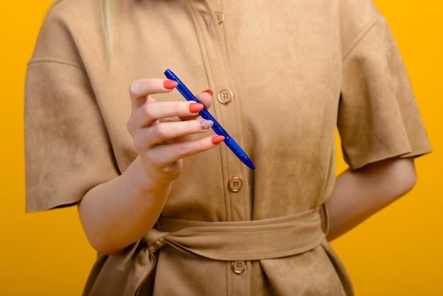Caneta na mão da mulher isolada em um fundo amarelo.