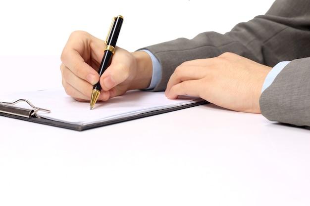 Caneta na mão escrevendo no caderno