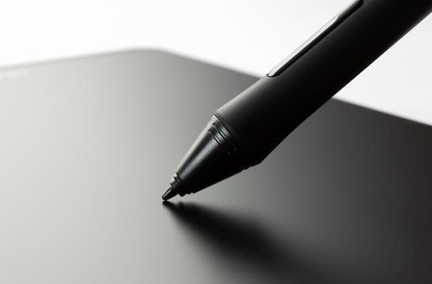 Caneta na mesa digitalizadora. vista lateral em fundo branco.