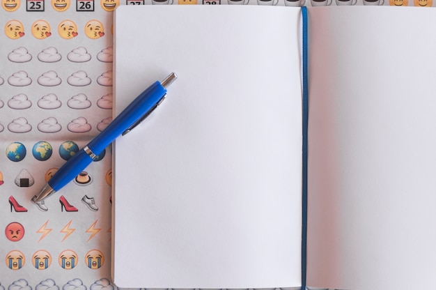 Caneta no bloco de notas e emoji