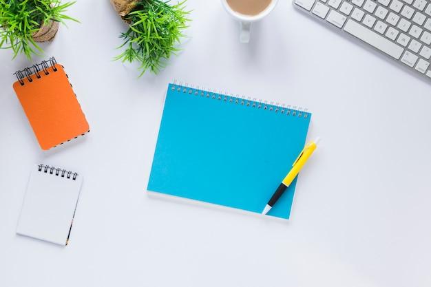 Caneta no bloco de notas em espiral com vasos de plantas; xícara de café e teclado em fundo branco